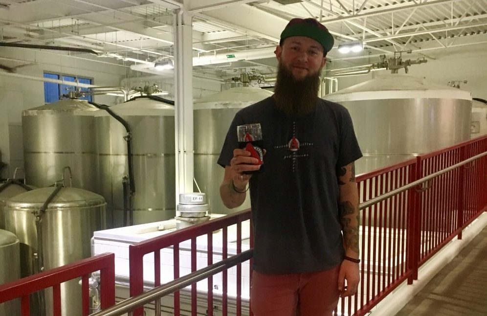 Cody standing in front of some big fermentation tanks at Avery