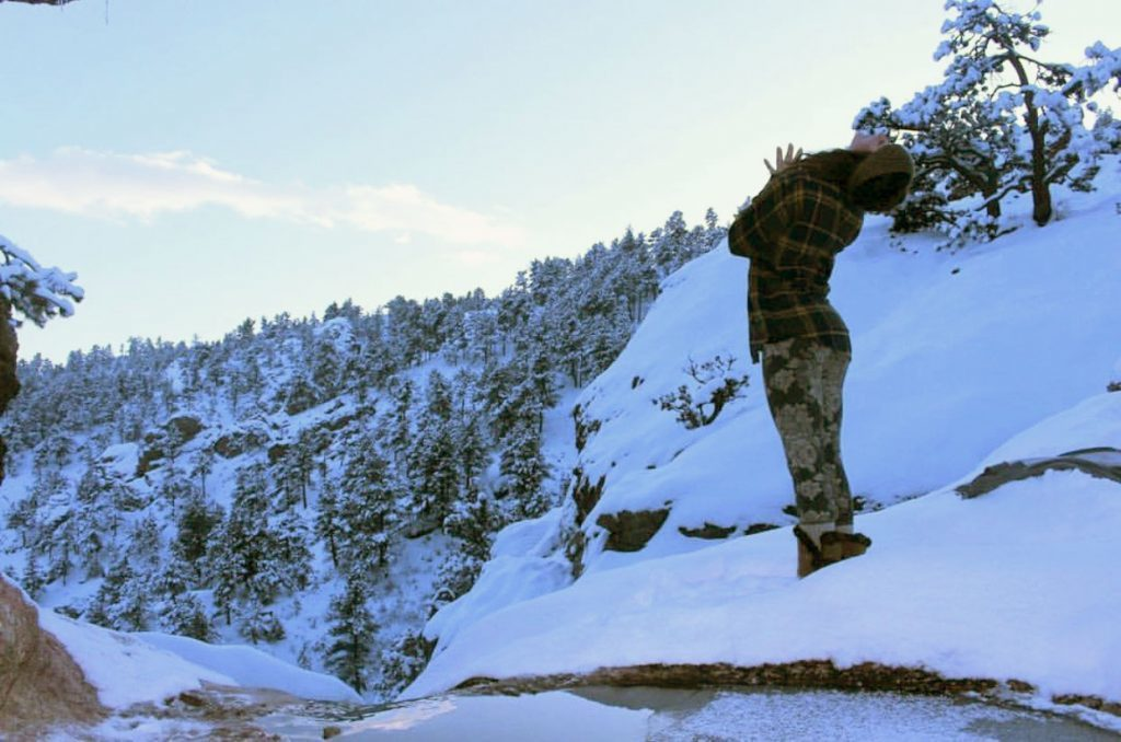 Taylor Trimarco does yoga on a snowy Colorado mountain top.
