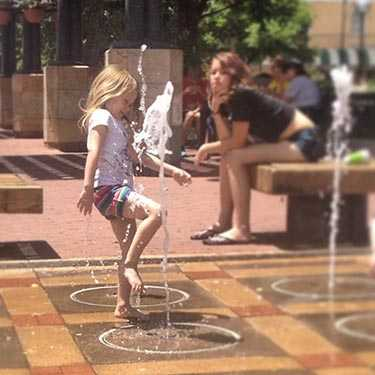 Little girl playing in downtown ground fountains.